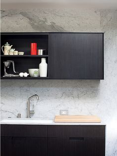 How the black cabinetry stands out against the marble wall and picks up on its veining, so it's not as stark a black/white contrast.