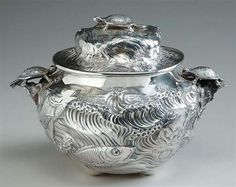 Gorham Aesthetic Movement Sterling Silver Two-Handled Covered Fish Soup Tureen  In the Japanesque style, of squat globular form, the body decorated with fish swimming in calm waters on one side and in turbulent waters on the other side, each aquatic themed handle surmounted with a cast and applied turtle, domed cover with conforming decoration and cast turtle finial.