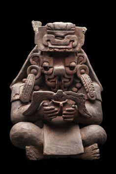1/ OAXACA - Urna del dios Pitao Cocijo. 60cm. Pluie et tonnerre. Position assise, en tailleur. Animal hybride, large nez, langue bifide évoquant une langue de serpent. Glyphe de sa coiffe associé à la pluie. Tient un récipient duquel surgit des pousses de maïs.