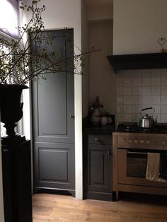 Continue wood floors, tile above stove, charcoal cabinets, black counters, vent hood cover, grey wall color