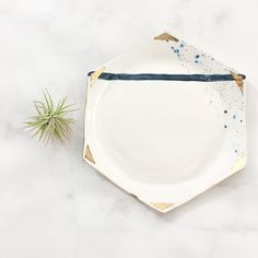 Adorned in real 22k gold luster, this hexagon rolling tray is the perfect accessory for any lady who is ready to up her smoking wares game. Proudly leave your tray sitting out for all to see, and get ready to rake in the compliments. Ready to ship!   THE BASICS  △ This rolling tray is hand crafted in Kansas City using porcelain clay.  △ Glazed in white with a blue speckled and navy stripe detail. 22k gold accents are then painted by hand and the piece is fired for the final time in the kiln…