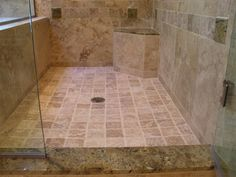 This travertine shower uses granite slabs and tiles as accents as well as the top for the seat and curb. Note how the granite accents on the wall are beveled squares that extend out about a quarter inch for a unique effect. The granite color is Typhoon Green.
