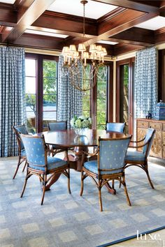 Architect Ken Brower's dining room addition to what is now the guesthouse features a coffered ceiling stained to match Tischler und Sohn mahogany doors that overlook the pool and waterway. PierceMartin chairs by Palecek in palm tree-printed upholstery surround a Touchwood UK table from England beneath a Niermann Weeks chandelier. The batik-patterned drapery fabric is by Raoul Textiles, and the rug is from Jack Walsh Carpets & Rugs.