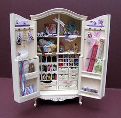 A Beautiful Collectors Accessorised Haberdashery Wardrobe for the ladies Sewing Room The Wardrobe is in cream with delicate floral sprays to the panels Inside the doors are filled with Rolls of Fabric and Lace. Cards with buttons, individual paper patterns and Memento's tucked behind ribbons To the main area we have tiny drawers filled with fabric,