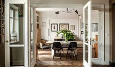 Folding wood-framed glass doors, designed by CHRAPKA, divide the living and dining rooms.