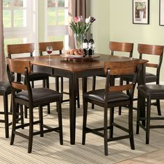 The counter height dining table features a beautiful oak and brown veneered top with a removable 18-inch leaf. Pair with matching counter height dining chairs.