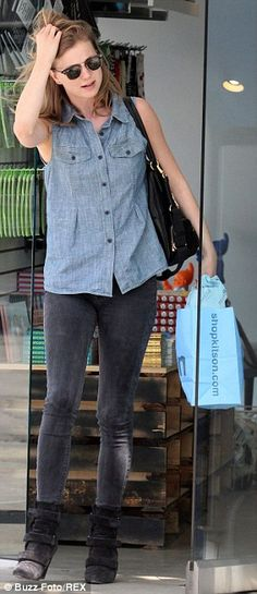 Hip in the city: Emily looked casual and chic in skinny black jeans, denim blouse and blac...