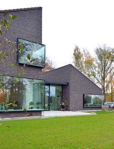 Large windows protrude away from the brown brickwork of this house in Belgium by Architektuurburo Dirk Hulpia, providing wide display ledges Brick Architecture, Residential Architecture, Contemporary Architecture, Modern Brick House, Modern House Design, Brick Facade, Facade House, Design Exterior, Brickwork