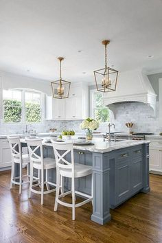 The windows on either side of the range hood add symmetry and extra light to this white kitchen. Not sure I particularly love the pendants, though.