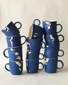 helen levi: This is as many of the 3rd edition of Cup Club™ as I could stack, it's a matte blue slip mug that's kind of like a reverse Cloud mug.