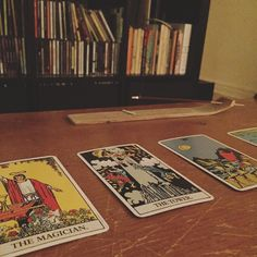 Just your average Saturday night [photo four tarot cards and incense on a table in front of a bookshelf]