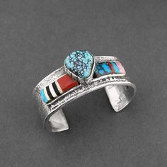 Cuff | John Shopteese (Potawotami).  Sterling silver, inlaid Jet, Mountain Turquoise, Red and Pink Coral.