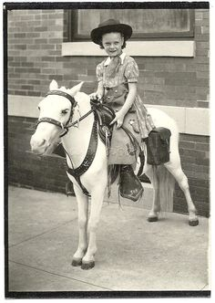 Vintage photograph of a girl on pony (perhaps a prop rather than a then-living horse). Props include a hat, saddlebag, and chaps or skirt with a horseshoe design. You may be interested inour other eBay listings .