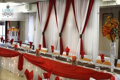 Red and white and orange fall wedding backdrop and head table draping with lights