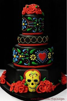 Day of the Dead cake by Ashley Trotter. ...I understand the skull is requisite, but I think this would be a cute cake with just the Mexican folk designs. The black background is such an unusual choice.