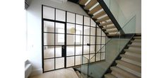 Internal glass partition and door in our Mondrian system and frameless glass balustrades to the stairs