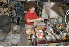Astronaut Sandra Magnus, Expedition 18 flight engineer, prepares to eat a meal at the galley in the Zvezda Service Module of the International Space Station.