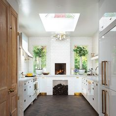 Food stylist Sasha Seymour gave her kitchen renovation a European flavor with a tiled hearth and open fireplace oven, dark herringbone wood floors, and raw wood doors. The high/low combo of vintage brass hardware and kickplates with white subway tiles continues to draw major love from design fans.