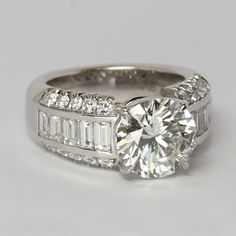 Round Brilliant Cut Diamond ring with channel set baguette diamonds by Oliver Smith Jeweler.