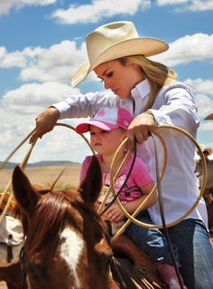 A rodeo cowgirl prepares to compete in the calf roping competition with her young daughter sharing the saddle at the annual Rodeo de Galisteo in...