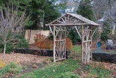 pergola en bois brut à l'entrée de l'allée du jardin