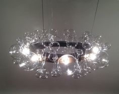 """""""circle light"""" chandelier made from handmade glass pieces and browned brass frame."""