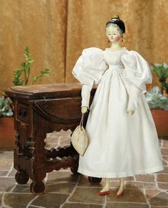 "17""-Very Fine Grodnertal Wooden Doll with Tuck Comb, Fine Painting and Original Costume~~~Comments: Grodnertal, circa 1840. Value Points: wonderful size with beautiful original painting, artistically rendered curls around the petite facial details, original gown, petticoat, and pantalets."