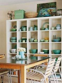 A collection of teal dishware transforms a storage area into a wall of art.