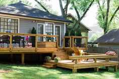 Veranda aus Holz mit Geländer aus Holzbalken und Stahlseil