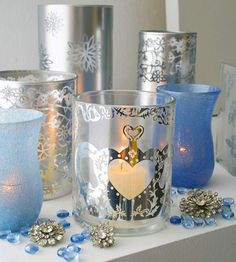 Metallic Candles Set a romantic scene with candles flickering behind silvery glass. Starting with plain cylinder cases or hurricanes, create designs with crafts store stickers, such as airy snowflakes and swirling Victorian motifs. In a well-ventilated area, spray the vases with silver metallic paint. When dry, peel off the stickers.