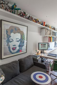 I Like the narrow ledge that runs along the length of the wall used to display a collection of mostly action figures(?) Keeps them neat, organized and out of the way - Paula & Paul's Lively London Home and Studio