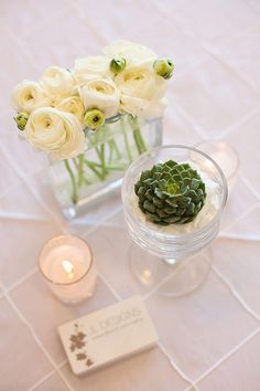 Elegant centerpiece  Feminine lines and curves, clean and simple florals in crisp whites, along with sand tones and aqua. A beautiful centerpiece in glass vases, filled with white crushed glass and a green succulent.