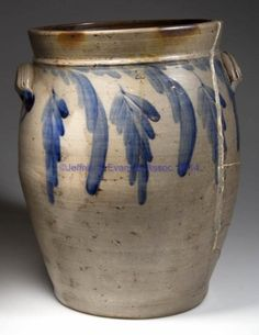 "VALLEY OF VIRGINIA DECORATED STONEWARE JAR, salt-glazed, ""4"" gallon capacity mark, ovoid form with a beaded ring below the flared collar and plain rim, large ribbed, arched handles. Brushed cobalt multiple dropped flower decorations on both sides, additional cobalt swags at handle terminals. Solomon Bell (1817-1882), Strasburg, VA. Circa 1850-1860. 14 1/2"" H, 10"" D rim. <BR><I>Large freeze crack off the rim on one side that is poorly filled, and three associated radiating…"