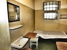 Weitere Innenaufnahme einer Zelle mit Blick auf das Bett und das Fenster, das nur ein wenig Licht, aber keinerlei Ausblick bietet.