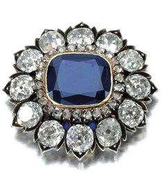 SAPPHIRE AND DIAMOND BROOCH/PENDANT, CIRCA 1880 Centring on a cushion-shaped sapphire within a frame of rose diamonds and a further border of circular-cut stones in foliate mounts, pendant loop, later detachable brooch fitting, fitted case.