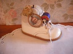 I love this baby shoe pincushion, with the spool of thread and the picture pin to the cushion.