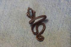 В данном мастер-классе хочу поделиться с вами техникой создания безразмерного кольца-змеи из проволоки. Змейка получается довольно необычная, в реальности смотрится интересно, а сделать такую своими руками из проволоки вполне по силам каждому. Итак, для работы нам понадобится: медная проволока диаметром 1,3/0,8/0,3 мм; бусина — каменнная (или любая другая) крошка; 4 медных бусинки диаметром 2 и 3…