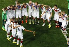 German players dance around the trophy as they celebrate after winning the World Cup final soccer match between Germany and Argentina at the Maracana Stadium in Rio de Janeiro, Brazil, Sunday, July 13, 2014. Mario Goetze volleyed in the winning goal in extra time to give Germany its fourth World Cup title with a 1-0 victory over Argentina on Sunday. (AP Photo/Fabrizio Bensch, Pool)