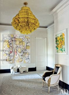 A Jacopo Foggini light fixture from Bernd Goeckler Antiques hangs in the entrance hall, which boasts paintings by George Condo (left) and Joan Mitchell as well as '60s French sheep otto mans from John Salibello Antiques and an Empire bergère (covered in a Stark leather) fromNewel.  DESIGNER: Susanna Maggard PHOTOGRAPHER: William Waldron