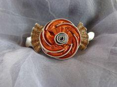Barrette pour cheveux réalisée à partir de capsules Nespresso orange et beige représentant une fleur et ornée de deux petites feuilles en metal argenté. Elle peut etre reali - 11004797