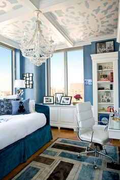 Feminine Blue Bedroom    Custom wall treatments in this blue bedroom extend to the ceiling, where a lacy pattern was stenciled for an ultra-feminine effect. A contemporary chandelier from Currey & Company lights the space, its texture complementing the clean lines on the bookcase, wooden flooring, and area rug.