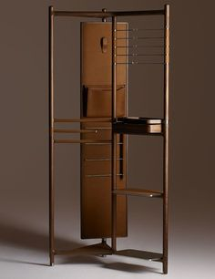 """The Groom valet is a stunning metal structure covered in Canaletto walnut. Its rotating mirror is backed in leather and equipped with a hook and a pocket, while stainless-steel bars and leather shelving provide additional storage. It measures 36"""" w. x 21.5"""" d. x 75.5"""" h.; $45,100."""