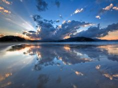 clouds mirrored on the surface of Waikawau Bay, Coromandel, New Zealand, by steve burling