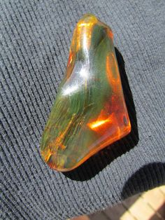 This is rare Green Amber from Chiapas, Mexico.  A high grade stone with amazing clarity and bright amber color. At certain angles and especially with a black background, it has an opalescent bright green color, almost looks like a gas running throughout.   It has been highly polished in its abstract natural nugget shape.   65mm long, by 33mm wide, by 20mm thick.  weighs 20.8 grams.  ships in a nice gift box.  Metric Conversion: 1/2 inch = 12 mm 1 inch = 25 mm 2 inch = 50 mm 3 inch = 75 mm 4…