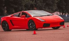 Drivers get behind the wheel of a Lamborghini or Ferrari with an instructor for laps around an autocross car-control course