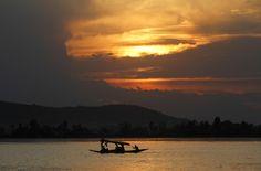 Turistas indios montan en un Shikara, un barco tradicional de Cachemira, en el lago Dal, como el sol se pone en Srinagar, India (Mukhtar Khan/AP)
