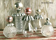 How's this for a tiny vintage bottle redux? Magia Mia has topped them off with tart tins turned upside down, then a tiny magnet glued on top of that, then a glass tree ball with the hook taken out - attached to the little magnet.  How cute!