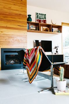 Living room with mid-century modern black sofa, colorful knitted throw blanket, and an indoor cactus