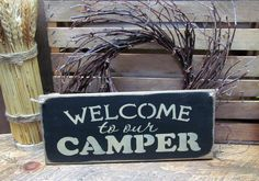 """This wooden camper sign is made from pine, and measures Approx 5.5""""W x 13""""L. It reads """"Welcome to our Camper"""". The front is painted Black then distressed, the back is stained . We've used a piece of j"""