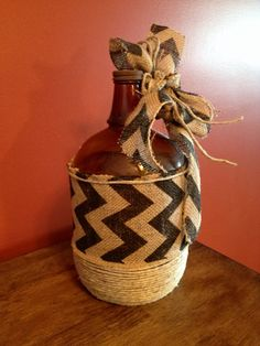 Found an old glass one gallon jug. Used some jute, burlap ribbon and hot glue gun to decorate.